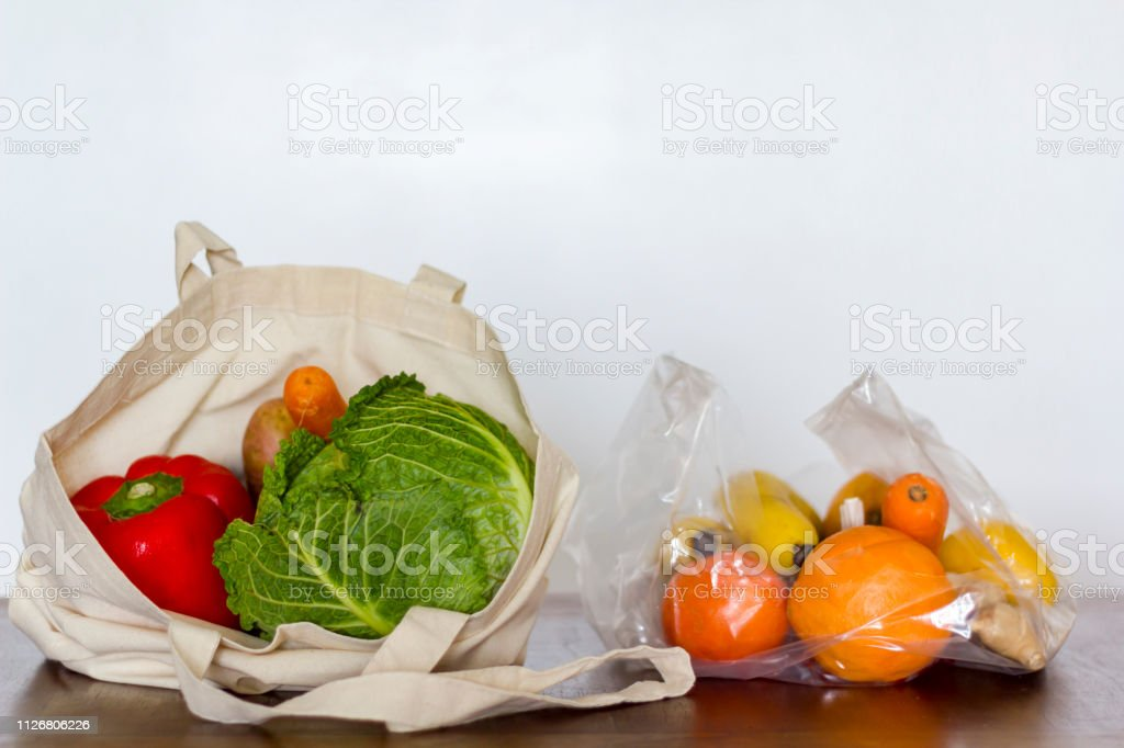 Eco reusable bag with vegetables vs plastic bag with fruits. Zero...