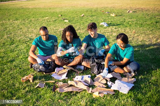 Eco volunteers sorting glass and paper waste on city lawn. Men and woman sitting on grass, picking up litter into plastic bags. Recycling concept
