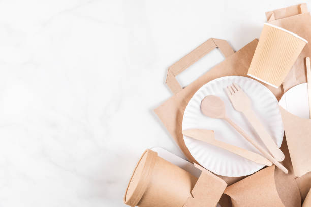 eco-friendly disposable utensils made of bamboo wood and paper on white marble background - bambù materiale foto e immagini stock