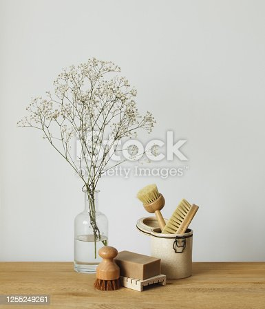 Natural wooden dish brushes and vase with flowers