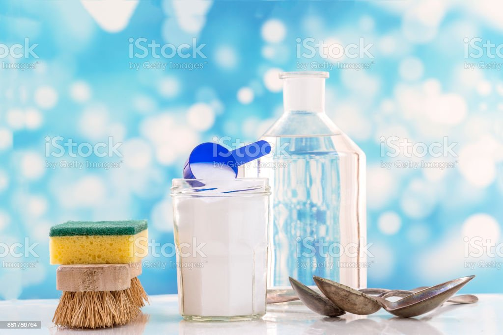 Eco-friendly natural cleaners baking soda, lemon and cloth on white and blue bubles background stock photo