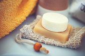 Eco-friendly shampoo bar without packaging on the washbasin with soap bags