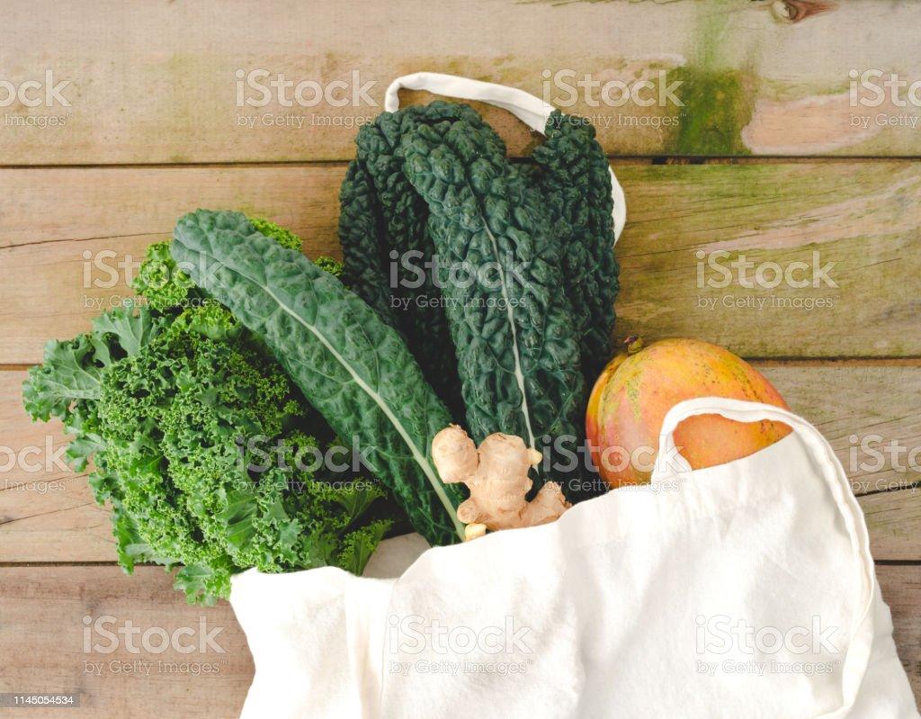 Sac en tissu écologique avec des légumes sur fond en bois rustique. - Photo