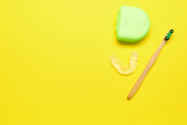 Ecological toothbrush and dental aligner with its box on a yellow background stock photo