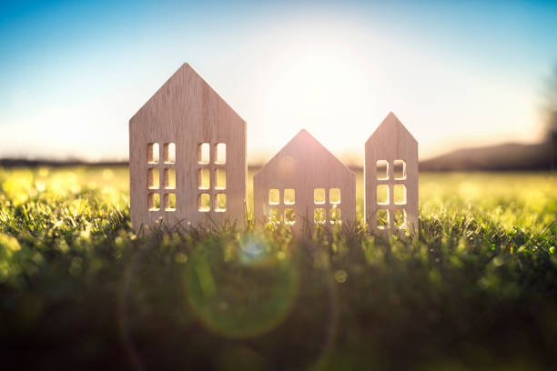 Ecological wood  model house in empty field at sunset Green ecological house in empty field at sunset concept for construction and real estate grounds stock pictures, royalty-free photos & images