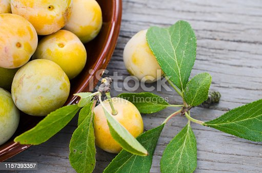 Ecologically grown yellow plums in a bowl. Close up of a pile of ripe sweet plums. The concept of harvest, gardening and healthy eating.