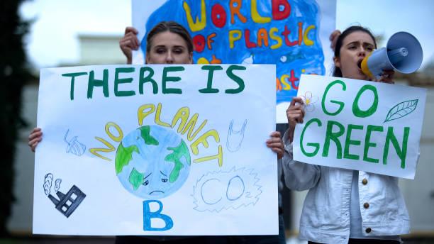 오염, 지구 온난화에 대해 메가폰으로 외치는 현수막을 들고 있는 생태학자들 - 기후 묘사 뉴스 사진 이미지