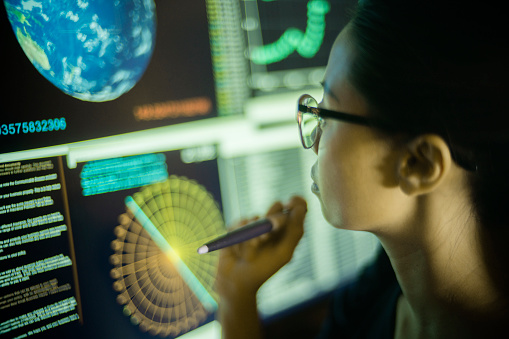 Stock photograph of a young Asian woman, pointing at, and learning from, global data displayed on a large computer monitor.