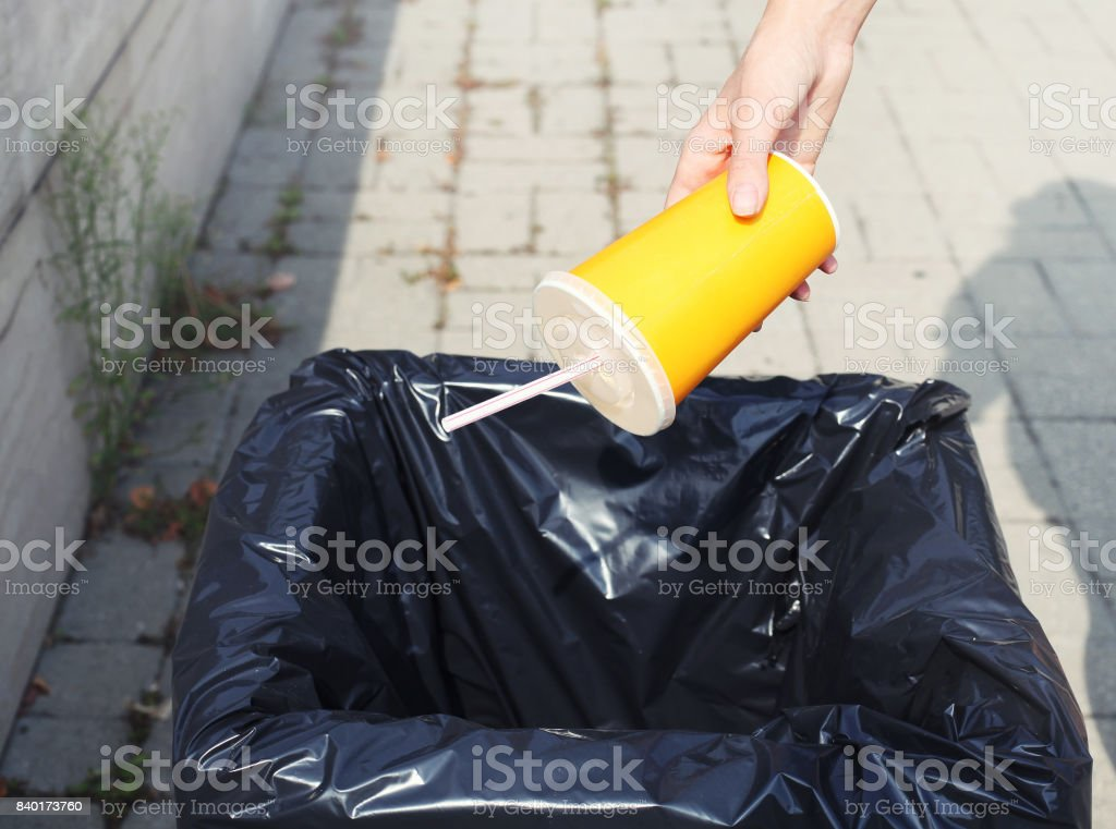 Ecology, environment, recycling concept - hand throwing plastic cup in trash on the street city stock photo