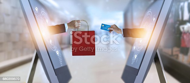 istock e-commerce, hand holding shopping bag and credit card from screen and global network 680359570