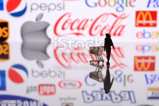 İstanbul, Turkey - February 12, 2014: Woman figurine with a shopping cart, standing in front of Apple iPad monitor displaying well-known world brands logos, including Apple, Coca-Cola, Mc Donalds, Google, ebay, Twitter, ups.