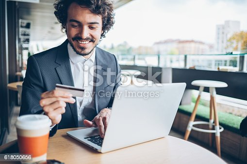 Smiling man sitting in cafe, holding a credit card and typing on a laptop, with copy space.