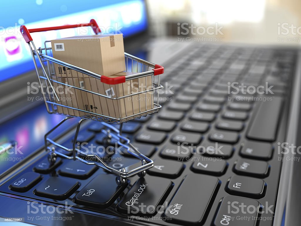 E-commerce. Shopping cart with cardboard boxes on laptop. stock photo