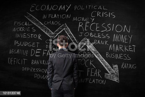 Economic crisis and related business therms word cloud written with chalk on black board. There is a big arrow chart moving down. A businessman seen from the back is looking at the blackboard
