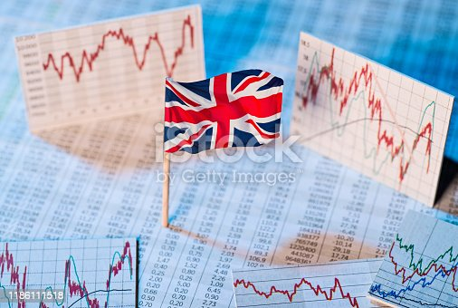 British flag with exchange rate tables and graphs on economic development
