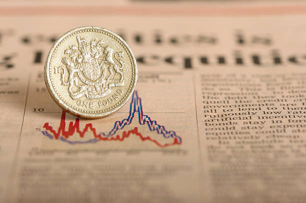 Economic down turn One English pound placed on a graph to represent an economic down turn bailout stock pictures, royalty-free photos & images
