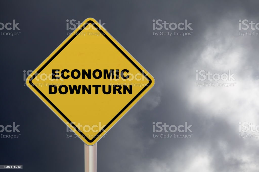 """Economic downturn - Crossing sign Diamond-shaped crossing sign with yellow background and black border with a short phrase saying """"Economic downturn"""" in the middle. Bankruptcy Stock Photo"""