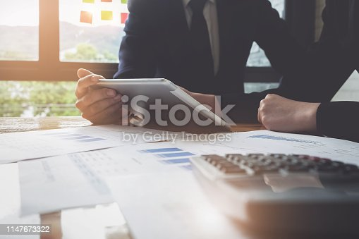 istock Economic research discussions, Business team analyzing income charts and graphs to plan marketing concept with using tablet and calculator  for analysis. 1147673322