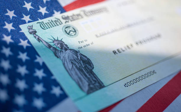 COVID-19 economic Stimulus check on blurred USA flag background. Relief program concept. Washington, DC, USA - March, 16, 2020: stimulus check stock pictures, royalty-free photos & images