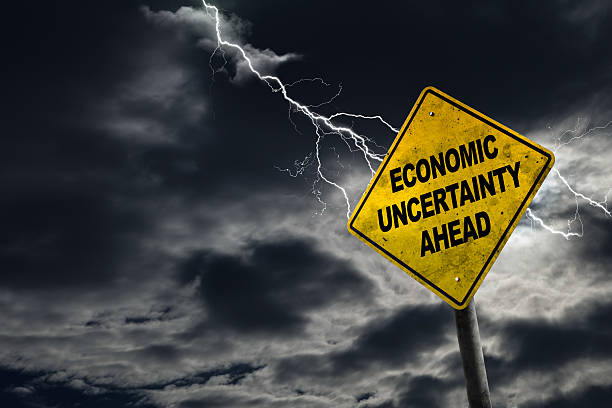 Economic Uncertainty Ahead Sign With Stormy Background Economic Uncertainty sign against a stormy background with lightning and copy space. Dirty and angled sign adds to the drama. recession stock pictures, royalty-free photos & images
