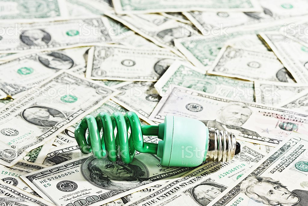 Economical, ecologically-sound green compact fluorescent lightbulb on many US dollars stock photo