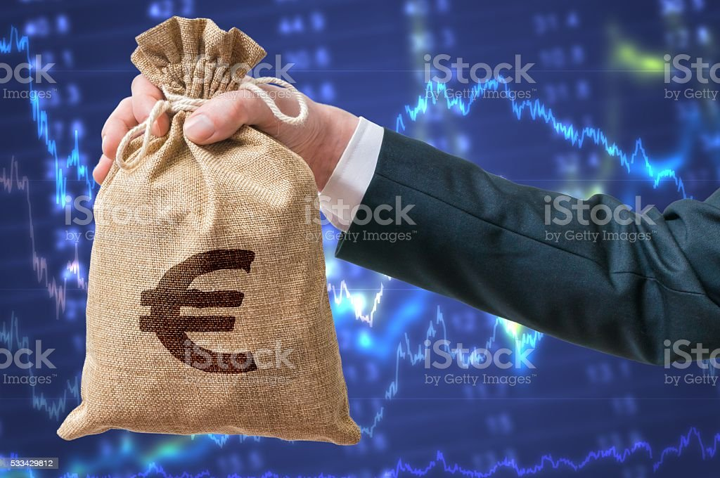 Economics of Eurozone. Businessman holds bag with money with Euro. stock photo