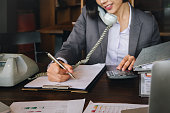 istock Economist and accountant, female working with document, computer laptop, calculator and using phone contact to customer in office. 1039315224