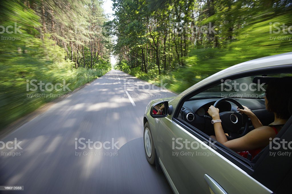 Economy car moving woman driving country road woods trees stock photo