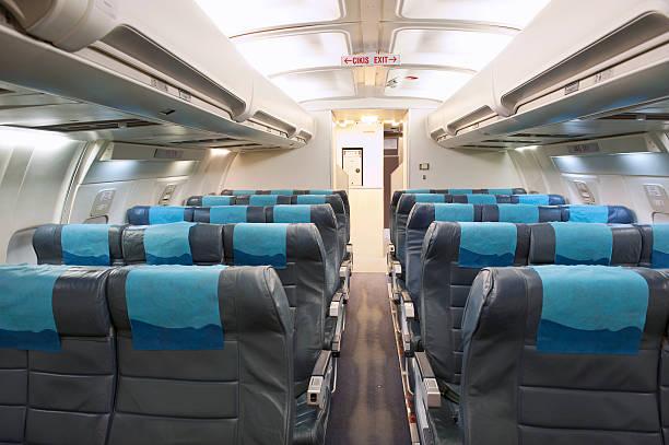 economy class-sitzbereich in einem flugzeug-kabine - kopfstütze stock-fotos und bilder