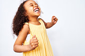 Portrait of African-American little curly haired girl in yellow dress laughing and dancing with closed eyes against white background