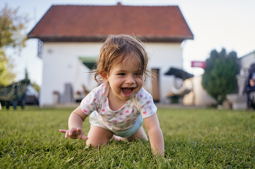 Beautiful innocent baby girl having fun playing in the back yard in summer on a sunny day.