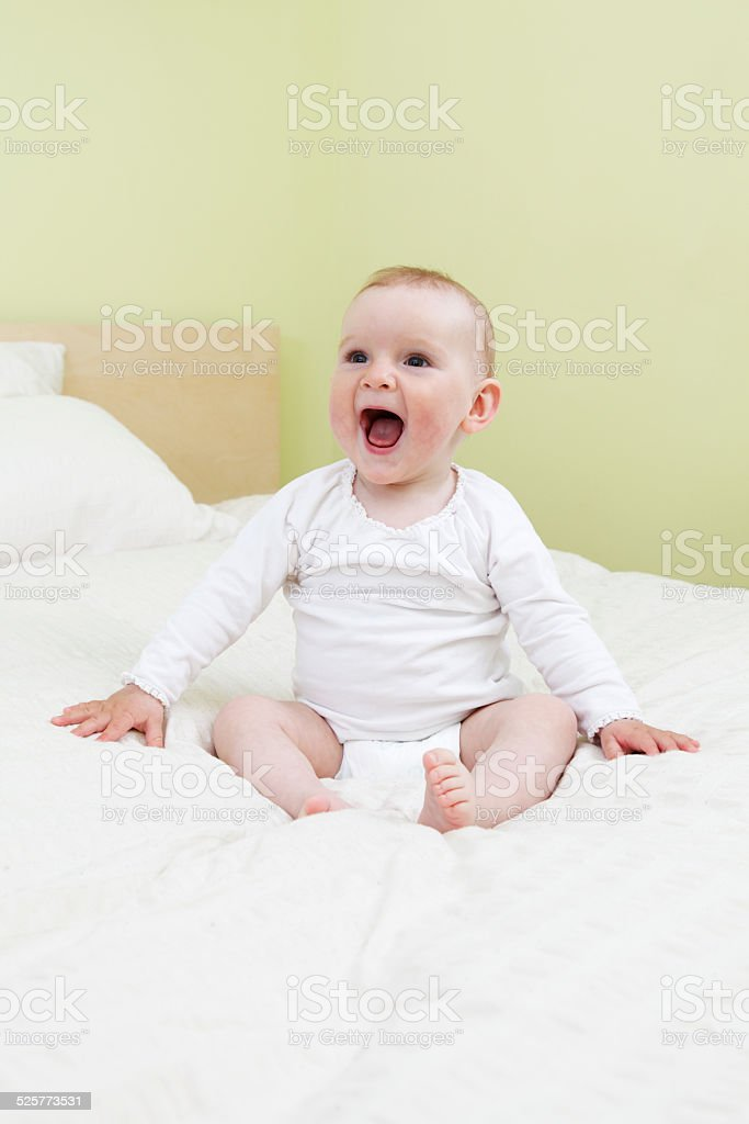 Ecstatic baby on bed stock photo