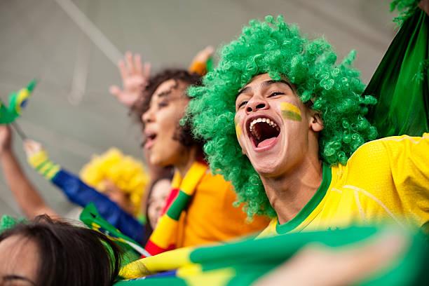 Ecstatic Brazilian fan watching a Football game stock photo
