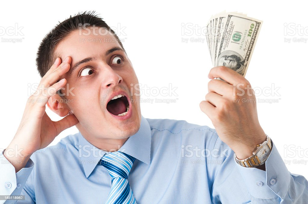 Ecstatic business man with big eyes, looking at dollars stock photo