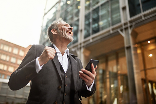 Low angle view of bearded Caucasian businessman in early 50s punching the air and smiling after reading good news on his smart phone in downtown London.