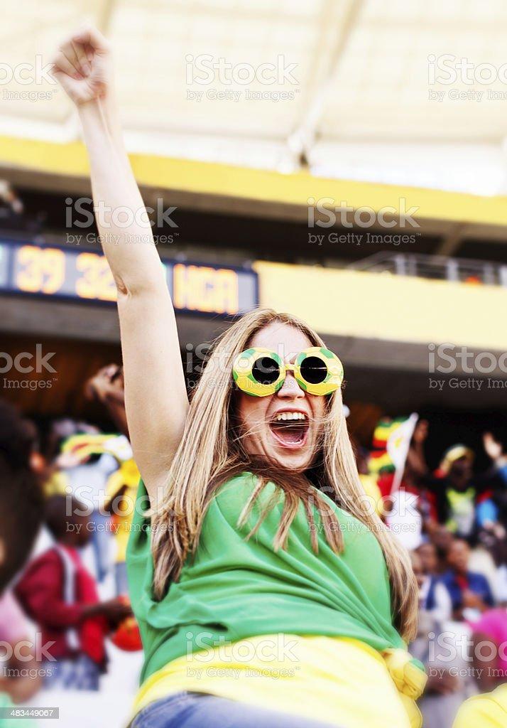Ecstatic female Brazilian soccer fan cheering on her team stock photo