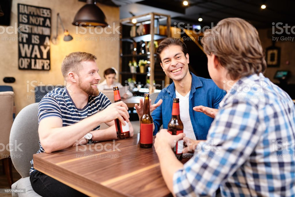 Jolly ecstatic young male friends in casual clothing, sitting at...