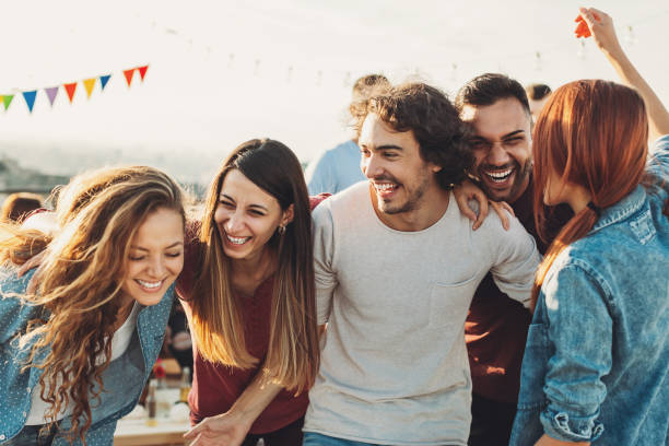 Ecstatic group enjoying the party Multi-ethnic group of young people on a rooftop party young adult stock pictures, royalty-free photos & images