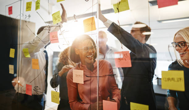 Ecstatic group of businesspeople celebrating together after a brainstorming session Diverse group of ecstatic businesspeople celebrating a winning idea together while brainstorming on a glass wall in a modern office brainstorming stock pictures, royalty-free photos & images