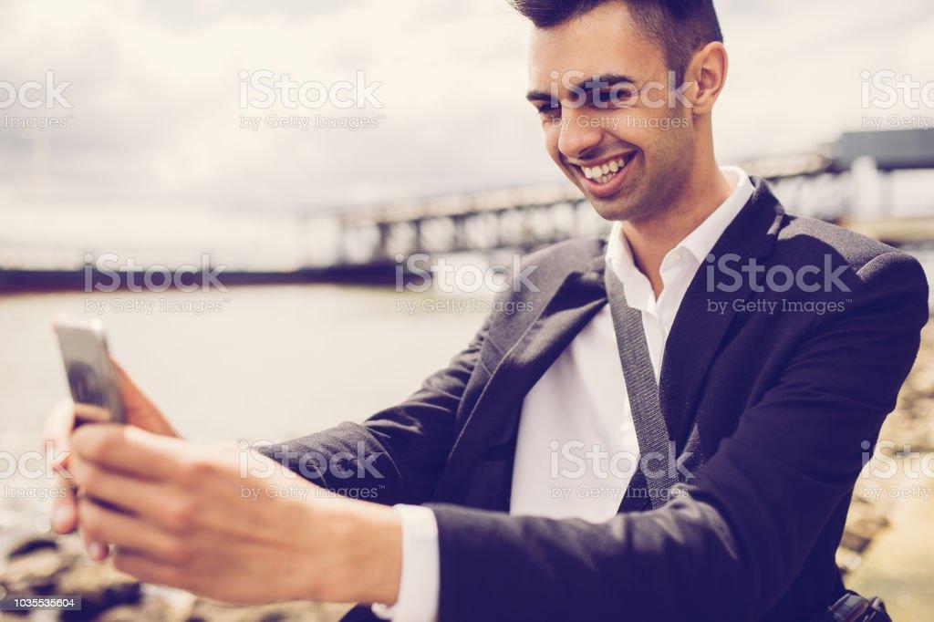 Ecstatic handsome male student taking selfie against riverside....