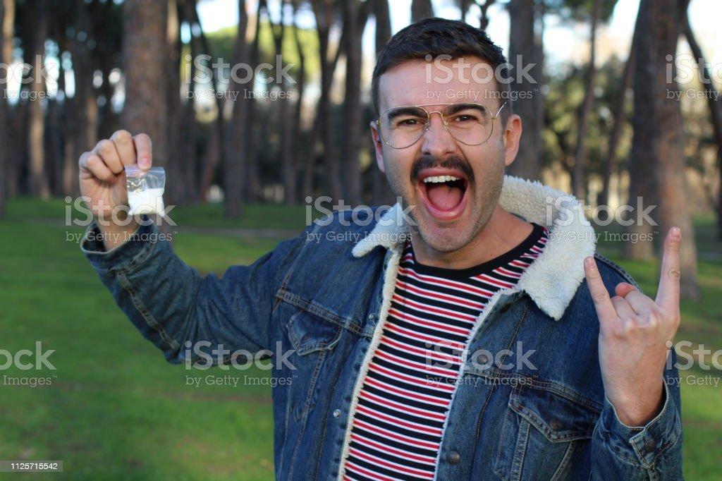 Ecstatic hip man showing cocaine bag.