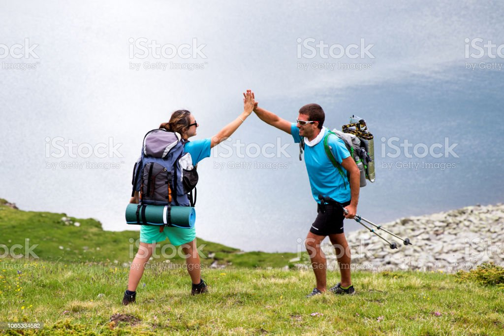 Young backpackers clapping hands in high five after a long trip in...