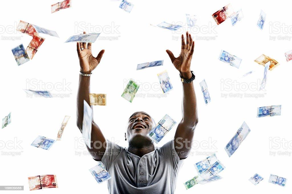 Ecstatic man catching raining banknotes stock photo