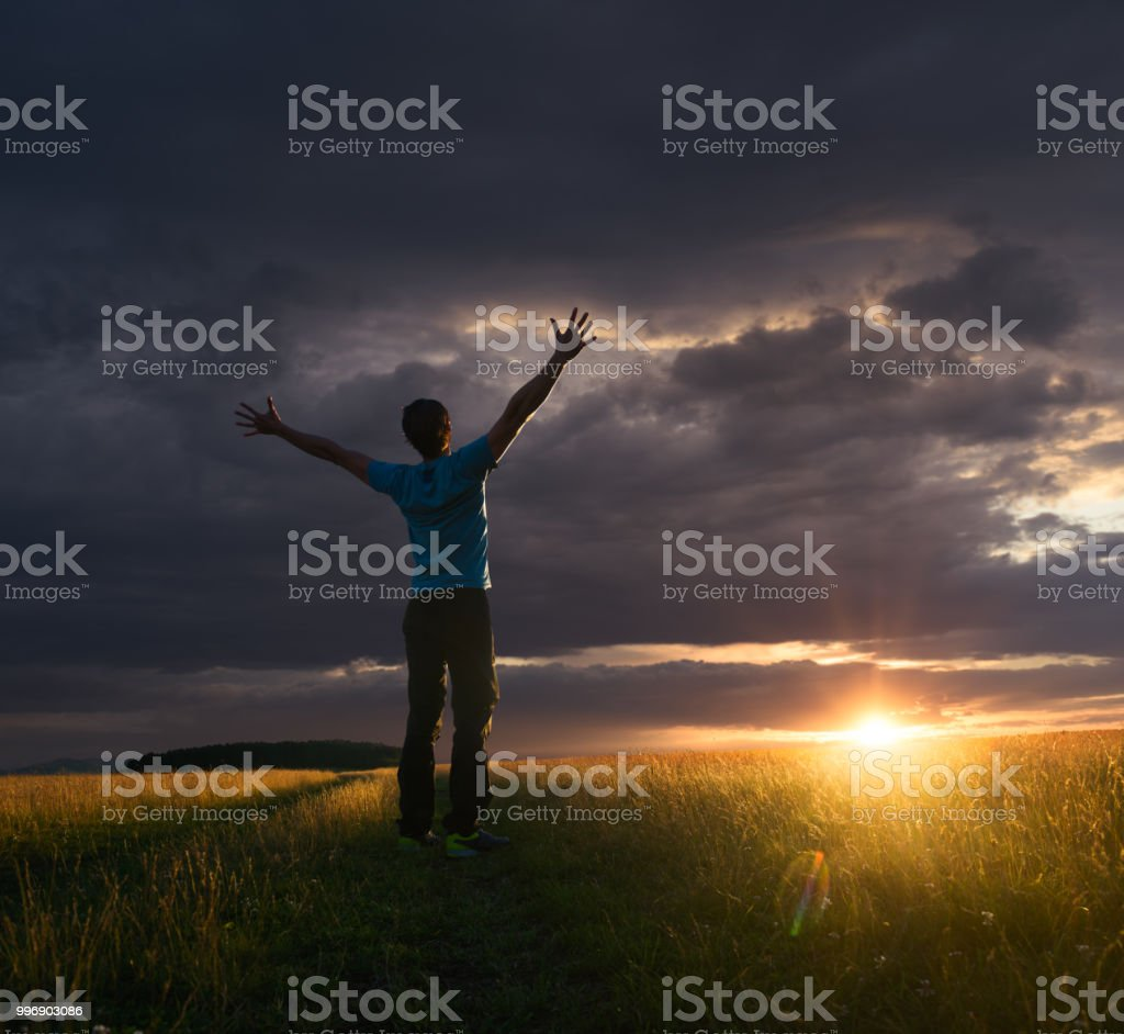 Ecstatic man greeting the sun at sunset after a heavy rain