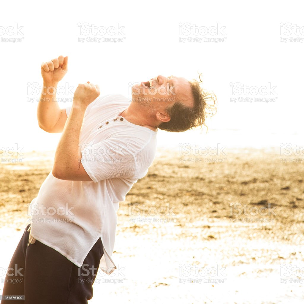 Ecstatic man hollering with joy while at beach holidays. He is turned...