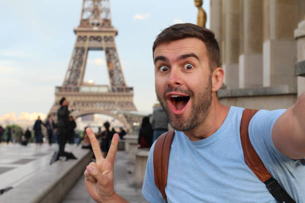Homem Ecstatic que toma um selfie na Torre Eiffel, Paris - foto de acervo