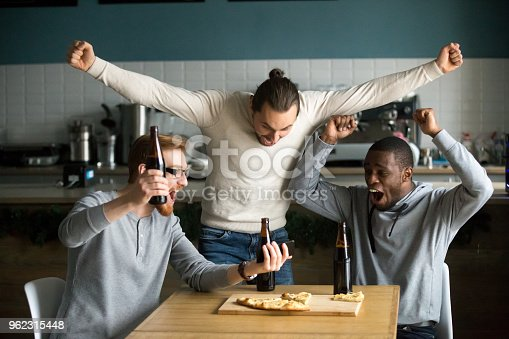Excited diverse men football fans celebrating victory goal score watching game online on smartphone supporting winning team drinking beer eating pizza together in pub, sport betting win concept