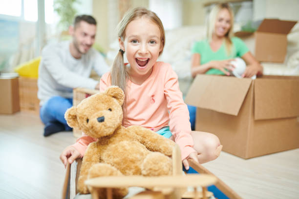 Ecstatic pretty daughter playing with teddy bear into new home and looking at camera, she keeping mouth open in excitement, her parents unpacking boxes in background stock photo