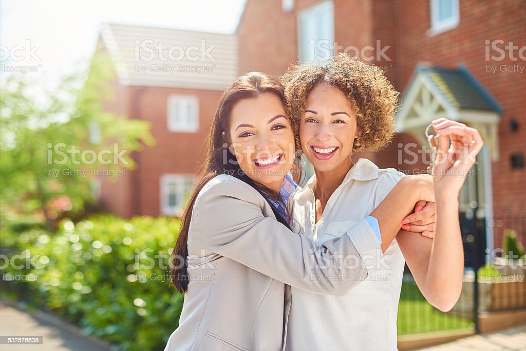 a young same sex couple celebrate getting the keys to their new house...