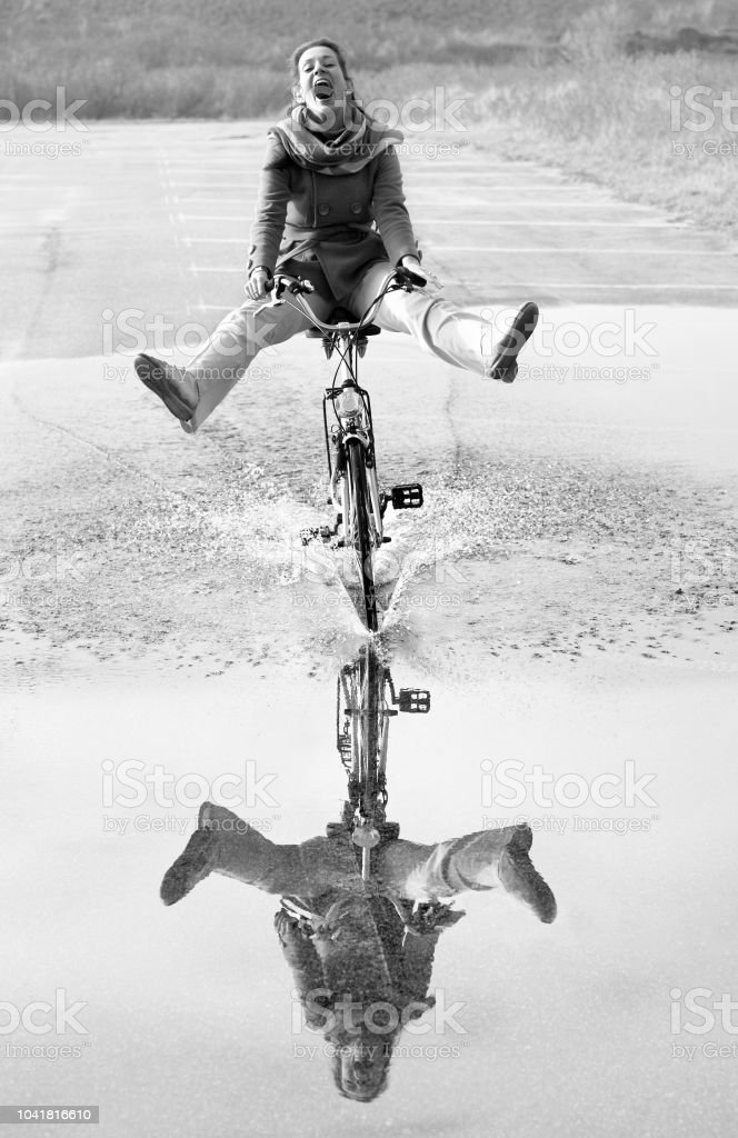 Ecstatic screaming mid adult woman cycling through puddle with...